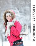Beautiful young Asian woman smiling happily as she walks through wintery countryside with her ice skates over her shoulder - stock photo