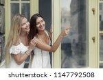 two pretty girls walking along... | Shutterstock . vector #1147792508