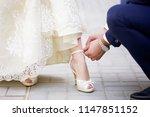 groom helps the bride to fasten ...   Shutterstock . vector #1147851152