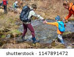 Mother Helps Child To Cross...