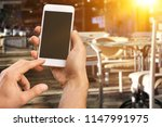 man using phone in cafe | Shutterstock . vector #1147991975