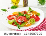 colored tomato salad with onion ... | Shutterstock . vector #1148007302