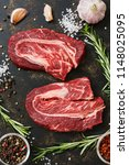beef raw steak on a dark rustic ... | Shutterstock . vector #1148025095