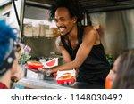 Smiling Food Vendor Hands Food...