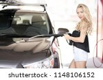 a blonde woman washing a suv car | Shutterstock . vector #1148106152