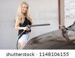 a blonde woman washing a suv car | Shutterstock . vector #1148106155