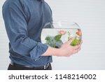 man carrying a dozen fish in... | Shutterstock . vector #1148214002
