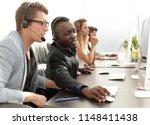 call center operators sitting... | Shutterstock . vector #1148411438