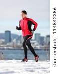 Fitness running man. Male runner training and jogging outdoors in winter snow with cityscape skyline. Workout and healthy lifestyle concept with Caucasian  fitness model in Montreal, Quebec, Canada. - stock photo