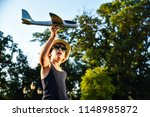 teenager playing with a plane | Shutterstock . vector #1148985872