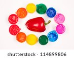 motley paints on the white background with vegetables. paints arranged in rainbow oval ring with red sweet pepper in the center. studio shot - stock photo