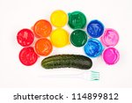 motley paints on the white background. paints arranged as rainbow with plastic fork partly colored in green paint and cucumber. studio shot - stock photo