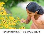 Little Girl Admiring Sunflower...