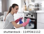 young woman cleaning oven with... | Shutterstock . vector #1149361112