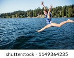 a happy girl jumping off the... | Shutterstock . vector #1149364235