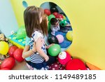 Stock photo caring young female teacher holding and guiding a shy pre school girl during free playtime in her 1149489185