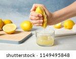 Woman Squeezing Lemon Juice...