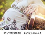 a very pregnant woman sits on a ...   Shutterstock . vector #1149736115