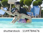 Teenage boy and girl playing in a swimming pool on a sunny day - stock photo