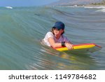 Teenage girl on a red and yellow kneeboard in the sea - stock photo