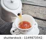 pouring hot tea on cup with pot | Shutterstock . vector #1149873542