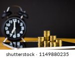 coins stacks and alarm clock in ... | Shutterstock . vector #1149880235