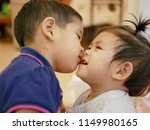 little asian girl kissing her... | Shutterstock . vector #1149980165