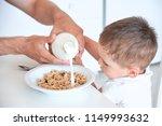 little boy helps dad pour milk... | Shutterstock . vector #1149993632