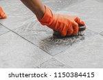 hand of man wearing orange... | Shutterstock . vector #1150384415