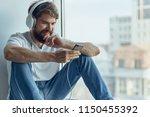 smiling man in big headphones... | Shutterstock . vector #1150455392