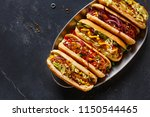Stock photo hot dogs fully loaded with assorted toppings on a tray top view 1150544465