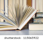 opened book close up with books in the back, selective focus - stock photo