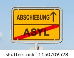 Small photo of yellow road or town sign informing in german that asylum is behind and deportation is ahead. Concept for national separation policy in Europe