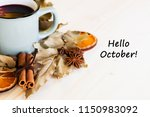 Small photo of Autumn, fall leaves, hot steaming cup of glint wine on wooden table background. Seasonal, autumnal hot wine, Autumn relaxing and still life concept. Top view with text hello october.