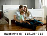 young parents reading book to... | Shutterstock . vector #1151054918