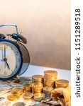 table clock and gold coin stack ... | Shutterstock . vector #1151289518