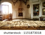Small photo of Retro old table place and home interior with window and fireplace. Free space for your decoration.
