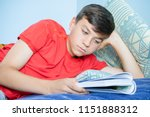 Caucasian teenage boy reading a book laying on a bed supporting his head - stock photo