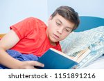 Caucasian teenage boy reading a book laying on a bed - stock photo