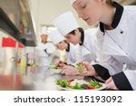 chef finishing her salad in... | Shutterstock . vector #115193092