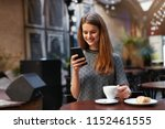 woman with mobile phone in cafe   Shutterstock . vector #1152461555