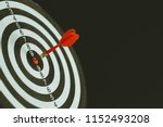 Stock photo red dart arrow hitting in the target center of dartboard 1152493208