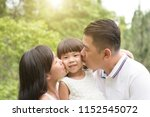 parents kissing daughter at... | Shutterstock . vector #1152545072