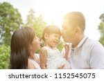 parents kissing child at green... | Shutterstock . vector #1152545075