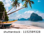 banca boat on shore under palm... | Shutterstock . vector #1152589328