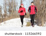 Sport couple running in winter. Runners jogging in snow in city park. Interracial young happy couple enjoying healthy lifestyle. Asian woman fitness model and caucasian man. - stock photo