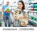 Stock photo young happy cheerful smiling woman with dog in pet shop during shopping with husband 1152814982