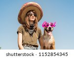 Small photo of Beautiful girl in mexican hat dressed up as bandit of gangster with dog in cool sunglasses. Female person in sombrero hat and bandana posing with puppy as mexico festive symbol or for halloween