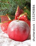 Christmas apple with a ribbon in the snow. - stock photo