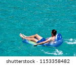 man floating on blue inflatable ... | Shutterstock . vector #1153358482
